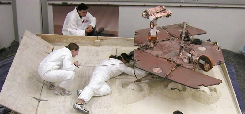 Члены команды Марс-ровера Скотт Максвелл, Паулин Хван и Ким Лихтенберг готовят тест-ровер для сессии 9 июля, целью которой является найти наилучший способ пересыпать мягкий грунт в специально собранный «мусорный контейнер» в лаборатории NASA. Результаты этого теста помогут инженерам создать стратегию для ровера NASA, который попал в затруднительную ситуацию на Марсе. (NASA/JPL-Caltech)