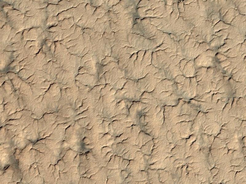 Этот снимок южного полярного региона Марса является частью серии фотографий, сделанных межпланетной станцией NASA Mars Reconnaissance Orbiter, в попытке отыскать модуль или хотя бы его парашют. Модуль был потерян после того, как вошел в атмосферу Марса в декабре 1999 года. Останки модуля могут быть покрыты пылью и льдом, что затрудняет поиски. Этот снимок был сделан 3 июля, а выпущен 8-го. (NASA/JPL/University of Arizona)