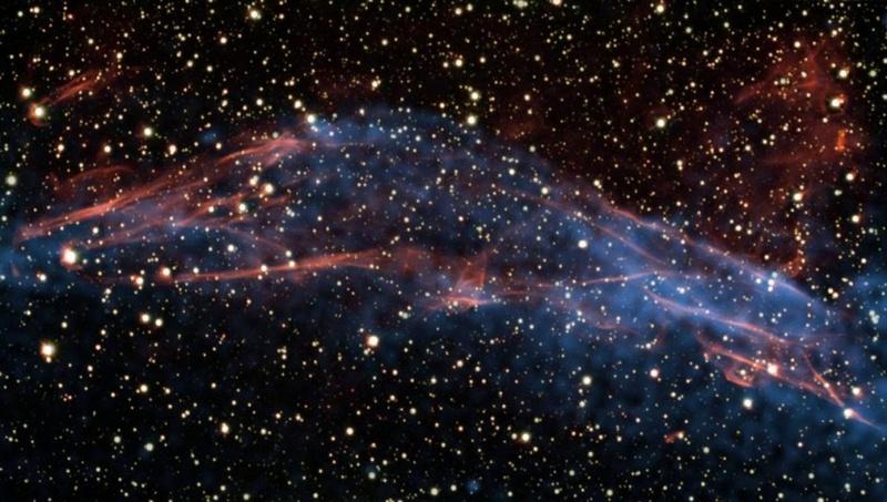 Космические лучи из галактики Млечного Пути эффективно ускоряются вслед за взорвавшейся звездой, как показано на этом снимке 25 июня, сделанном с помощью большого телескопа Южноевропейской обсерватории и обсерватории NASA Чандра. Ученые изучали цветные коды излучений из остатков сверхновой RCW 86, которая находится на расстоянии в 8 200 световых лет от Земли, чтобы узнать, как работает этот «сверх-ускоритель». Они обнаружили, что взрывная волна, созданная звездным взрывом, движется со скоростью от 1 до 3% скорости света. (ESO/NASA/CXC)
