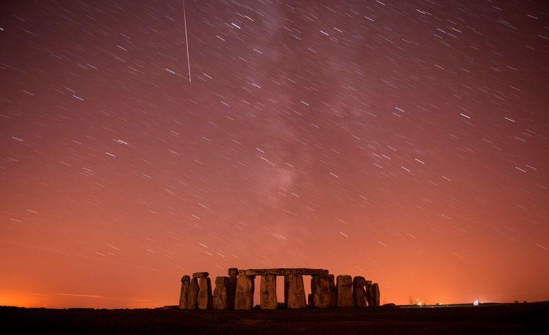 Метеор проносится мимо звезд в ночном небе над Стоунхенджем в Англии 12 августа. Персеиды возникают каждый августа, когда Земля проходит через поток космических обломков, оставленных кометой Свифта-Туттля. Фото сделано с помощью длинной экспозиции. (REUTERS/Kieran Doherty)