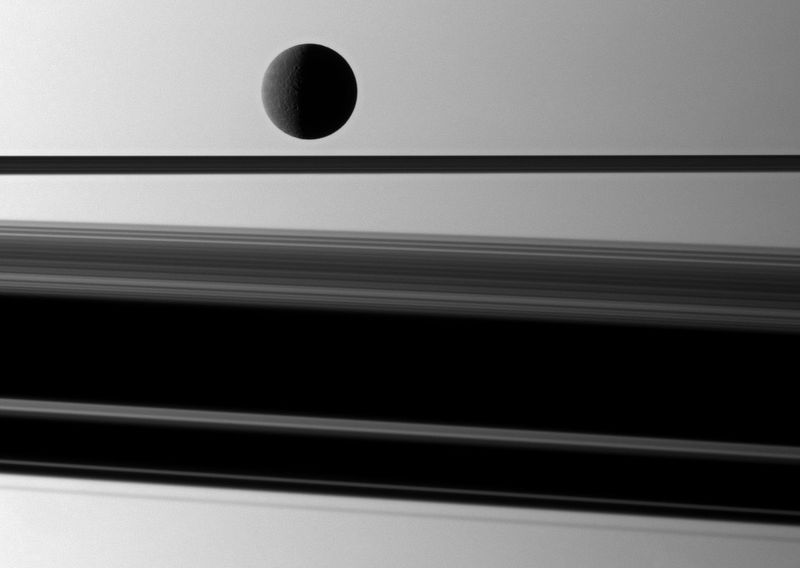 Спутник Сатурна Рея (1528 км) слегка подсвечивается перед планетой с широкой тенью, которую отбрасывают кольца Сатурна, 8 мая. (NASA/JPL/Space Science Institute)