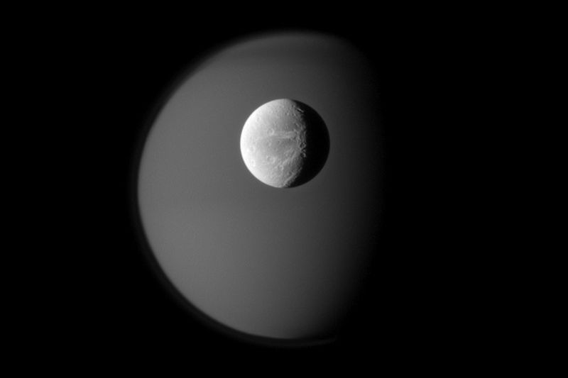 Поверхность спутника Сатурна Дионы на фоне туманного призрачного Титана 10 апреля. Снимок был сделан аппаратом «Кассини» на расстоянии приблизительно 1,8 миллионов км от Дионы и 2,? Миллионов километров от Титана. (NASA/JPL/Space Science Institute)