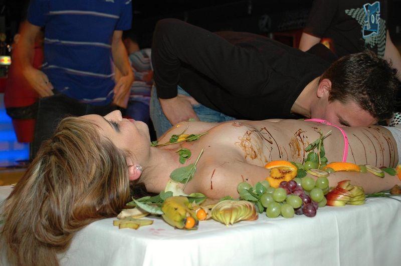 голая девушка украшенная едой в ресторане нее