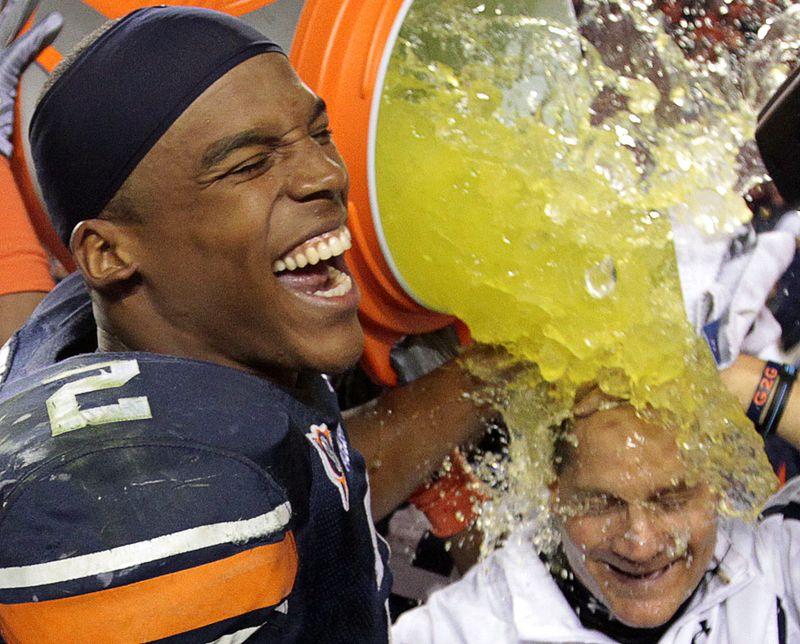 Камерон Ньютон (слева) из команды «Auburn» обливает своего тренера после победы над командой «Georgia», 13 ноября, Алабама. (AP Photo/Dave Martin)
