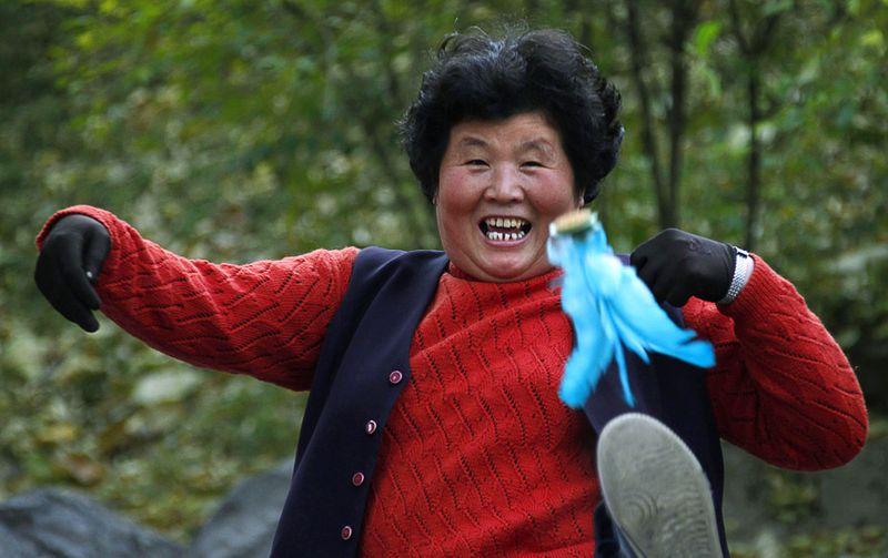 Женщина во время игры «jianzi», смысл которой заключается в том, что необходимо ногами перебрасывать небольшой мешочек с бобами друг другу, Пекин, 14 ноября. (REUTERS/Petar Kujundzic)