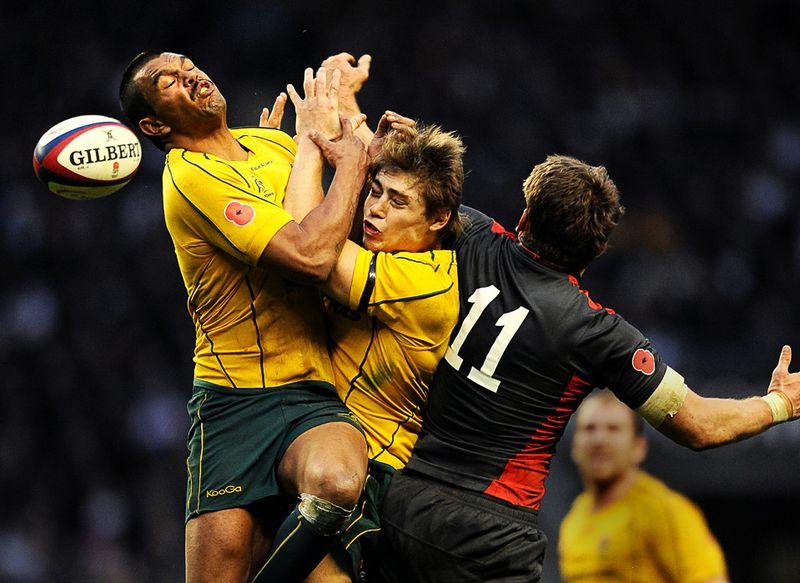 Столкновение австралийских игроков Кертли Била (слева) и Джеймса О'Коннера, попытавшихся помешать взять мяч английскому игроку Марку Кето во время матча по регби в Лондоне, 13 ноября. (ADRIAN DENNIS/AFP/Getty Images)