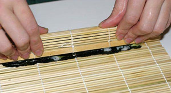 Совместите нижний край водоросли с краем бамбукового коврика. Теперь, удерживая начинку на месте, поднимите край коврика с помощью больших пальцев, как показано на фотографии вверху. Продолжайте поднимать коврик вверх и вперед, пока его край не упрется в противоположную сторону водоросли. Загните край коврика наверх, покатайте ролл вперед-назад и немного сожмите его внутри коврика. Прижмите торцы ролла пальцами, если оттуда выпал рис. Отложите ролл в сторону на гладкую поверхность, и приступайте к изготовлению следующего.