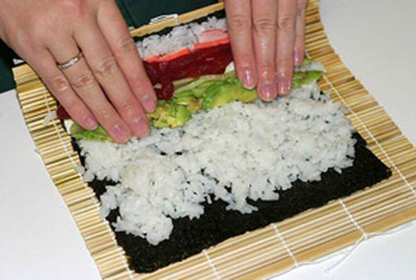 Удерживая все ингредиенты, поднимите край коврика с помощью больших пальцев и продолжайте поднимать его вверх и вперед, пока край коврика не коснется противоположного края водоросли. Затем, загните край коврика наверх, и