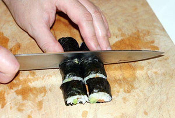 3. Как разрезать роллы. Возьмите острый нож, и окуните его кончик в уксусную воду. Затем, поверните его острием вверх, так чтобы вода пробежала по всей поверхности ножа и равномерно смочила его. Это позволит ножу легко пройти сквозь липкий рис и не застрять в нем.