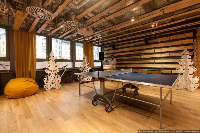 В холле стоит стол для настольного тенниса, на стене виден экран, на нем можно поиграть в видеоприставку.