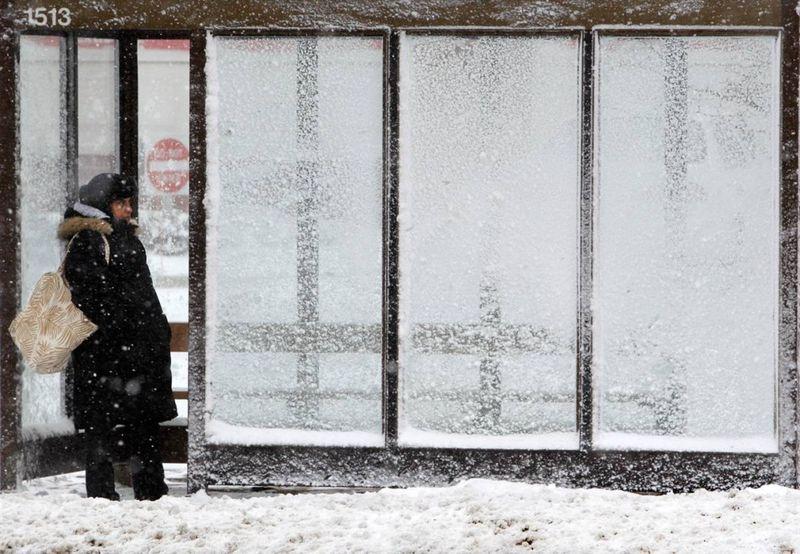 2. Женщина ждет автобус в Мэйфилд Хайтс, штат Огайо, 13 декабря. Морозы и сильные снегопады вызвали хаос на дорогах и задержки авиарейсов. (Tony Dejak / AP)