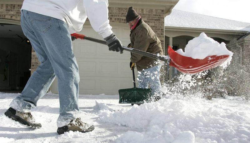 4. Райян Шоу (слева) и Джефф Мессенджер убирают снег с дорожки в Боулинг Грин, штат Огайо. (JD Pooley / AP)