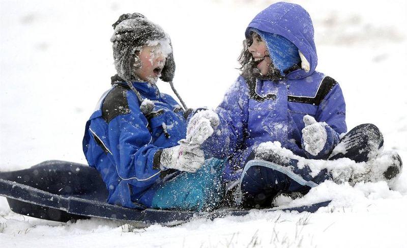 8. Эбби Уоткинс смеется над другом Хоупом Грегори, получившим снежком в лицо, в Боулинг Грине, штат Кентукки. (Joe Imel / Daily News via AP)