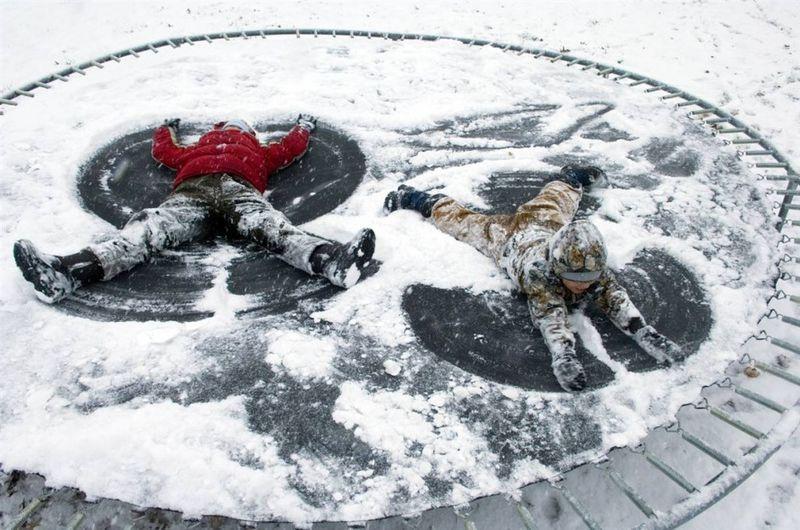9. Ханна Киссел (слева) с братом Итаном нашли способ использовать батут в зимнее время на заднем дворе своего дома в Сент-Джозефе, штат Индиана. (Denny Simmons / The Evansville Courier & Press)