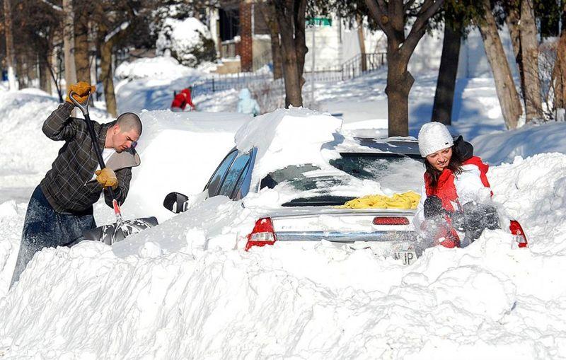 12. Патрик Кейс и Джесса Себелко разгребают автомобиль из сугроба в Ю Клэйр, штат Висконсин, где выпало 55 сантиметров снега. (Steve Kinderman / Eau Claire Leader-Telegram)