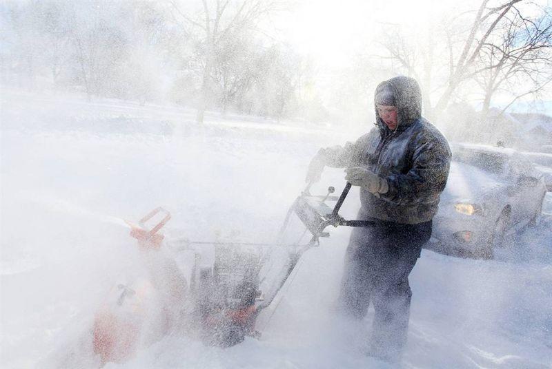 13. Майкл Стивенс убирает снег снегоочистителем вокруг автомобиля соседки в Вайноне, штат Миннесота. (Andrew Link / Winona Daily News)