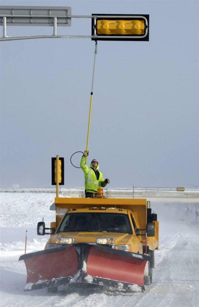 14. Дэн Холл счищает снег со светофора самодельным скребком в Весн Бенде, штат Висконсин. Он и другие работники департамента общественных работ днями и ночами убирают снег с городских дорог. (Rick Wood / Milwaukee Journal-Sentinel)