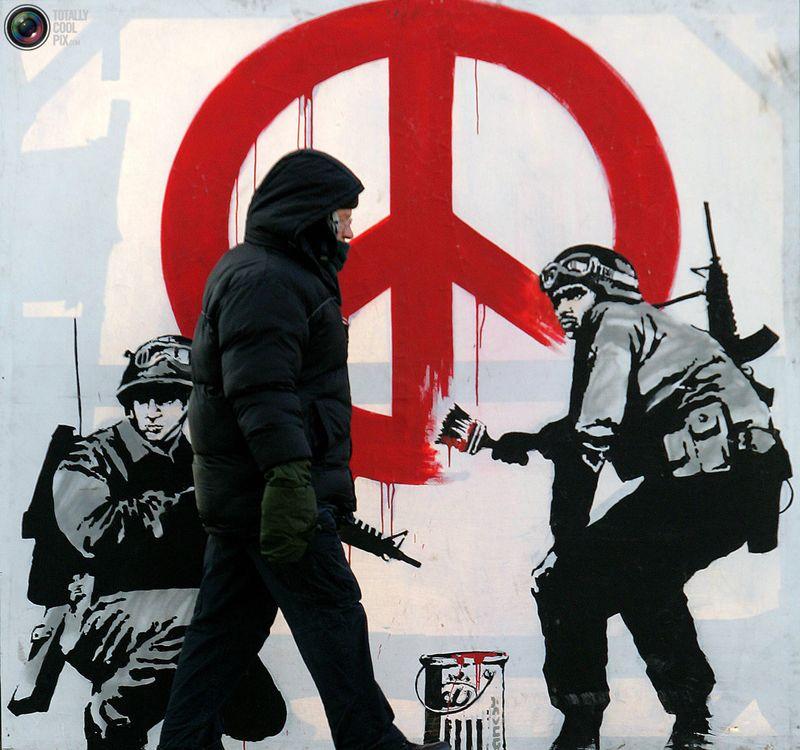 Мужчина проходит мимо антивоенного граффити британского художника Banksy на Парламентской площади в Вестминстере 28 февраля 2006 года.