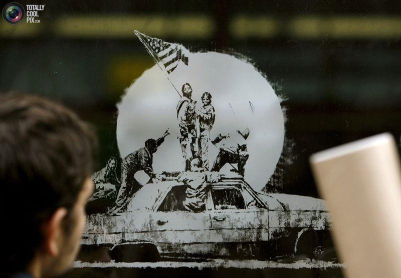 Прохожий смотрит на новый принт художника Banksy под названием «Флаг» в очереди у галереи Сантас Гетто в Лондоне 18 декабря 2006 года.