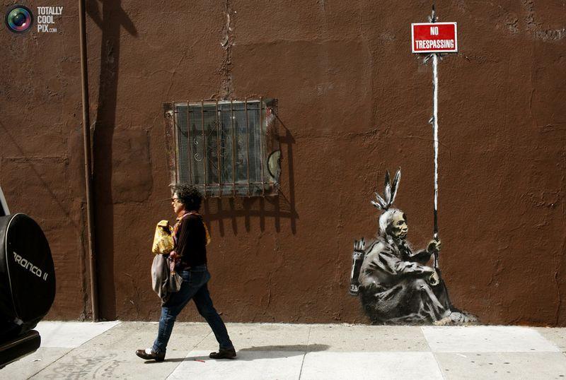 Женщина проходит мимо одной из работ Banksy в Сан-Франциско, Калифорния, 4 мая 2010 года.