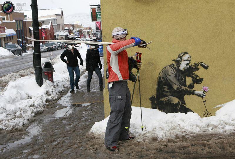 Лыжница смотрит на произведение искусства от Banksy на стене здания в Парк-Сити, штат Юта.
