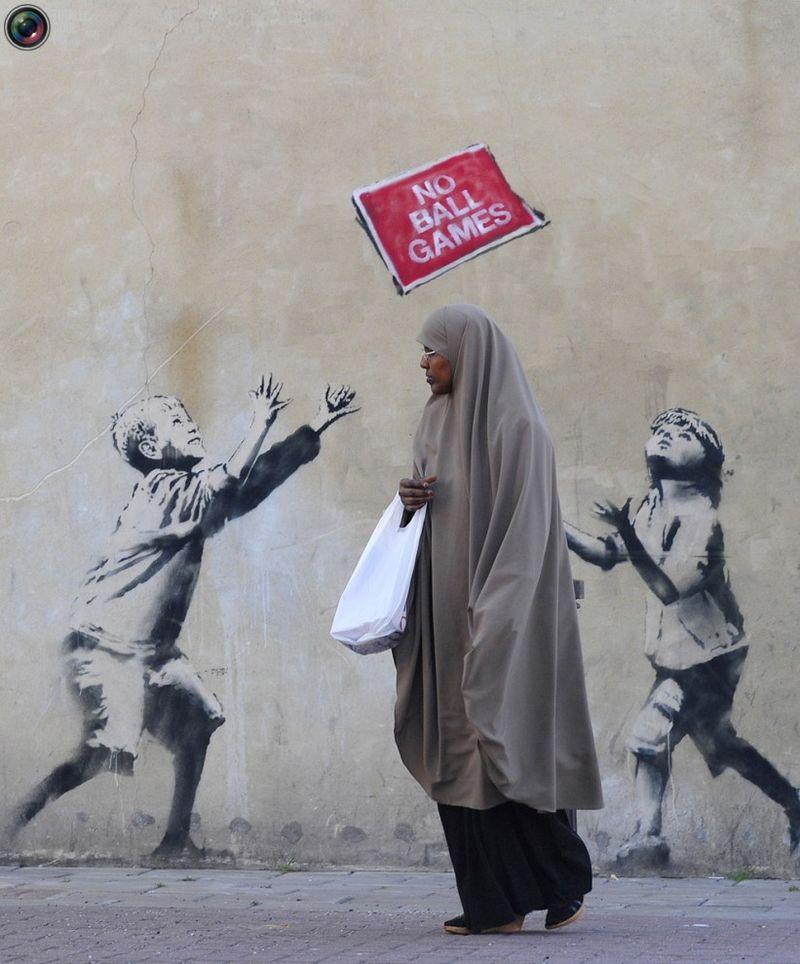 Женщина проходит мимо очередного граффити в стиле Banksy в Лондоне 24 сентября 2009 года.