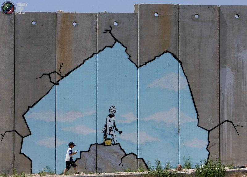 Палестинский мальчик проходит мимо граффити от Banksy недалеко от контрольного пункта Каландия на Западном берегу реки Иордан, 10 августа 2005 года.