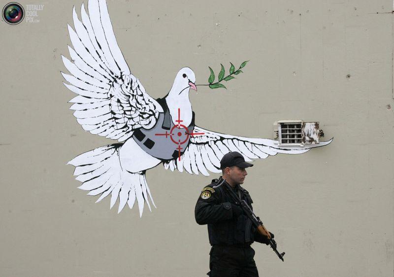Член палестинских служб безопасности перед рисунком Banksy во время визита президента США Джорджа Буша в город Вифлеем 10 января 2008 года. Буш приехал с визитом на Западный берег реки Иордан, где проходил конфликт между Израилем и Палестиной по поводу границ.