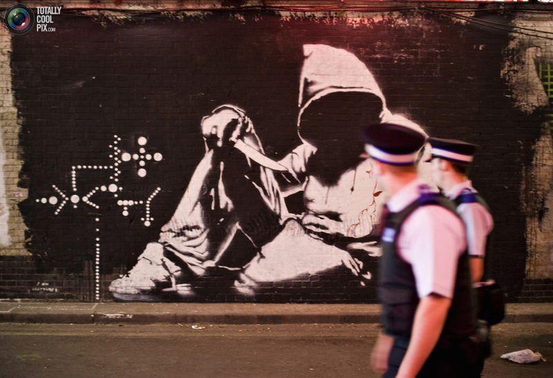 Полицейские смотрят на граффити от Banksy на стене тоннеля от станции метро Ватерлоо в Лондоне 23 июня 2008 года. Неиспользуемый туннель на юге Лондона стал местом проведения огромной общественной выставки британского граффити-художника Banksy. Теперь здесь можно найти работы различных граффити-мастеров.