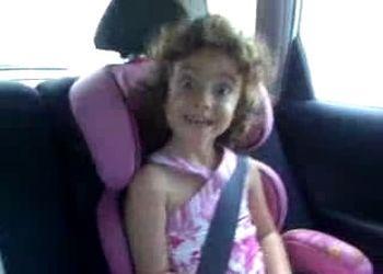 Девчушка кривляется на заднем сиденье