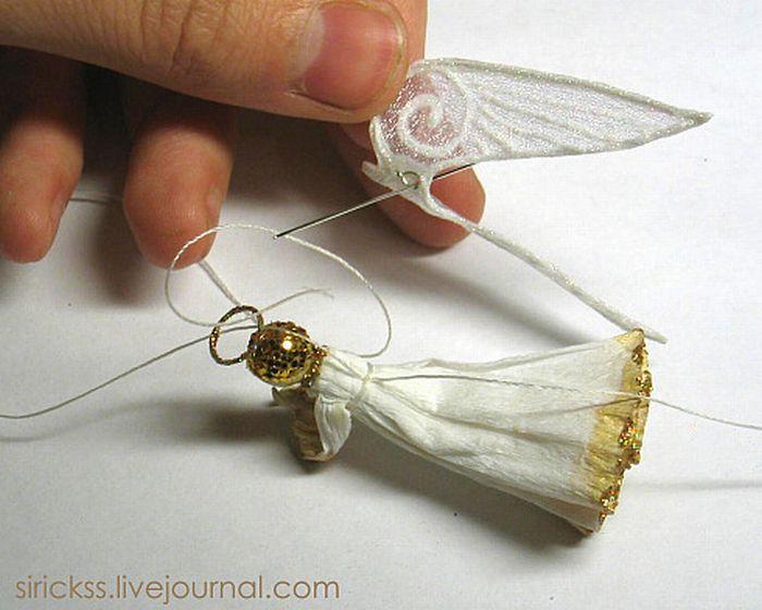 Крылья прошить ниткой, обвязывающей ангела, через проволочную петельку, при этом надо сделать несколько узелков и закрепить их клеем. Затем отрезать один из концов нитки.  Для уверенности перед пришиванием крыльев можно капнуть клея на место соединения.