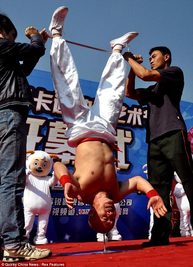 Каскадер Ли Синь из Китая простоял на голове 10 секунд на шипе (3 фото)